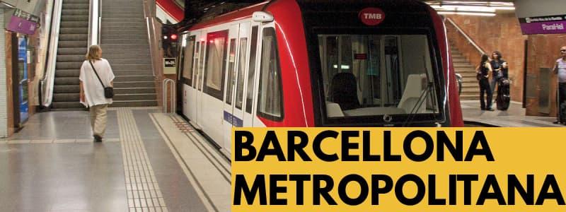 Fotografia di una stazione della metropolitana di Barcellona con il treno in arrivo ed una persona che sta uscendo dalla stazione ed altre che parlano con rettangolo in basso a destra arancione e scritta nera Barcellona Metropolitana