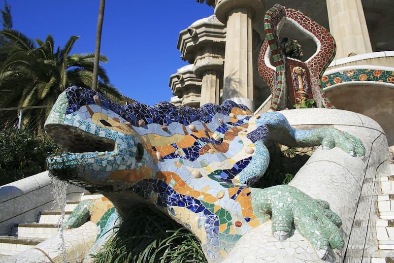 Scultura di una lucertola ricoperta da mosaici colorati tra due scalinate di Parc Güell