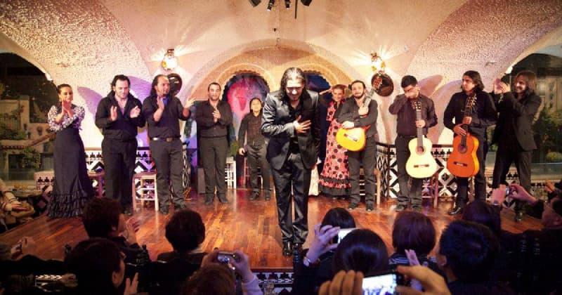 Fotografia del palco del locale Tablao Cordobes a Barcellona. Sul palco c'è un ballerino di Flamenco e dietro di lui diversi musicisti. In basso c'è il pubblico