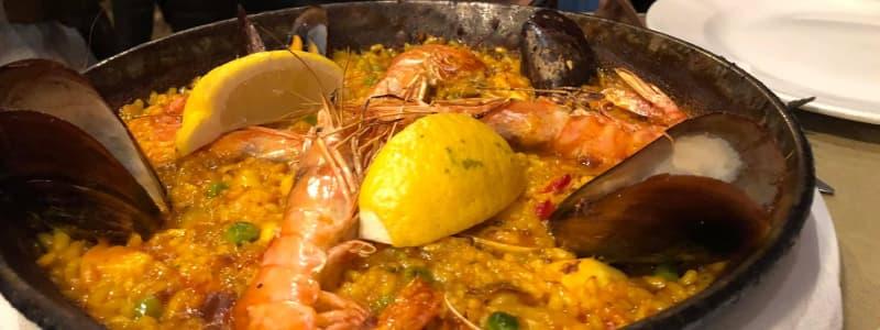 Fotografia ravvicinata paella spagnola con limone gamberi e cozze