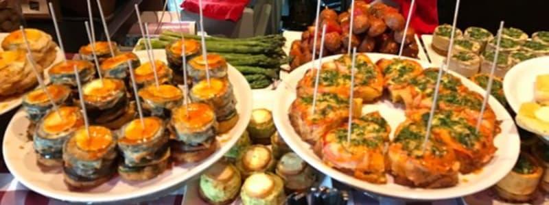 Fotografia ravvicinata di più piatti in tavola di Tapas condite in modo diverso
