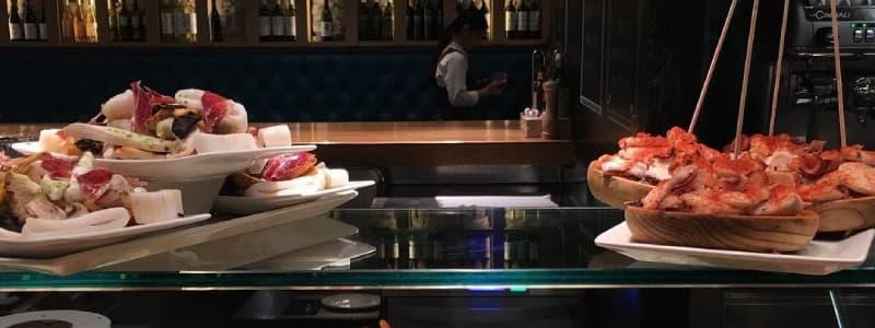 Fotografia di due piatti di tapas spagnole su un bancone in vetro in un locale