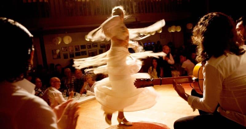 Fotografia di una ballerina di Flamenco vestita di bianco e di un musicista con chitarra sulla destra e pubblico in un locale