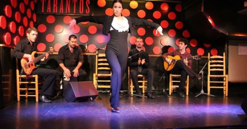 Fotografia di una ballerina di Flamenco su un palco con gruppo di musicisti alle spalle con sfondo nero e rosso
