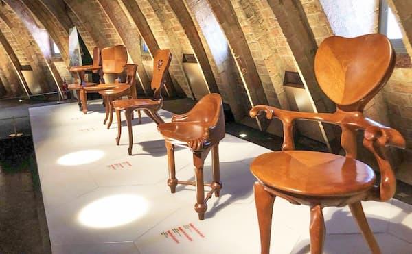 Fotografia di alcune sedie disegnate da Antoni Gaudi per casa Milà esposte su una piattaforma con descrizioni accanto a loro