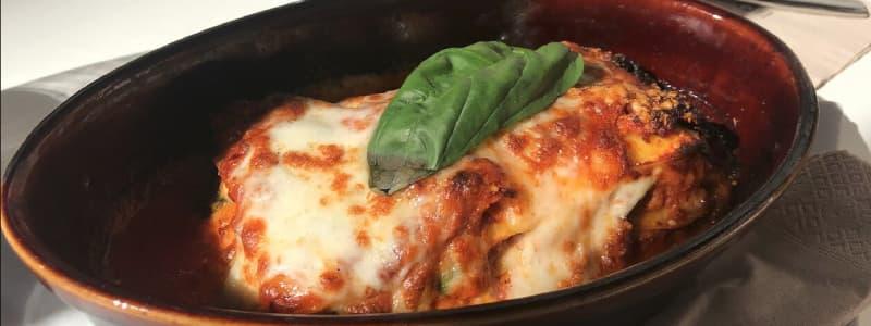 Fotografia ravvicinata di un piatto con pomodoro mozzarella e foglia di basilico su un tavolo