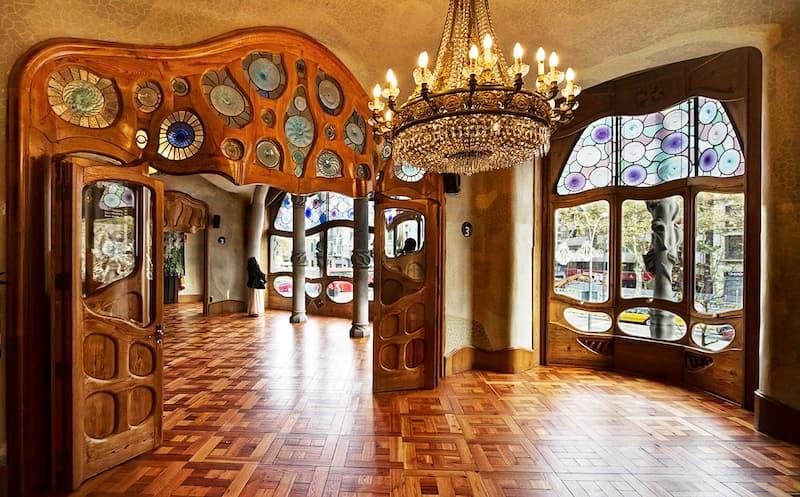 Fotografia dell'interno di Casa Milà di Barcellona con parquet in legno, candeliere con luci accese e decorazioni in legno alle porte e finestre
