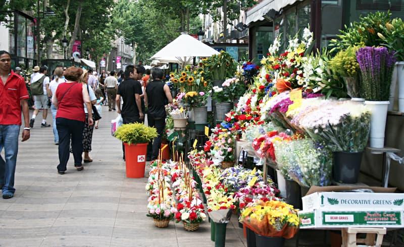 Fotografia di una bancarella che vende fiori sulla destra con persone che camminano sul lato sinistro della Rambla de Les Flors di Barcellona