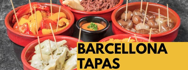 Fotografia di diverse tapas mette in ciotole piccole rosse con un condimento in un'altra ciotola nera al centro e rettangolo arancione in basso a destra con scritta Barcellona Tapas