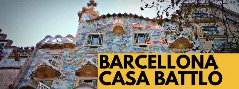 Fotografia dell'esterno di Casa Battlo a Barcellona con il muro decorato con motivo floreale e rettangolo arancione in basso a destra con scritta nera Barcellona Casa Battló