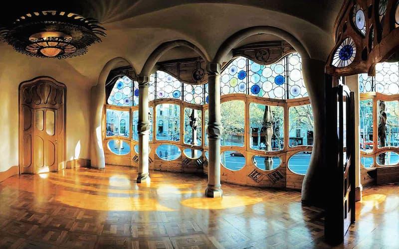 Fotografia dell'interno di Casa Battló a Barcellona con parquet, finestre di vetro e colonne