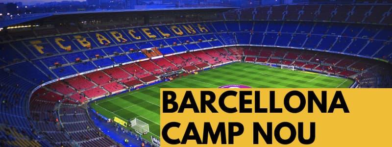 Fotografia dall'alto del campo di calcio Camp Nou di Barcellona con spalti rossi e blu con scritto in giallo Barcelona e rettangolo arancione in basso a destra con scritta nera Barcellona Camp Nou