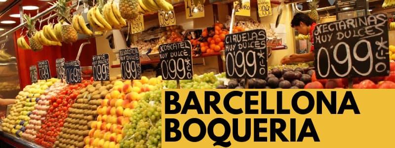 Fotografia di una bancaerella di frutta con i prezzi esposti e rettangolo arancione in basso a destra con scritta nera Barcellona Boqueria