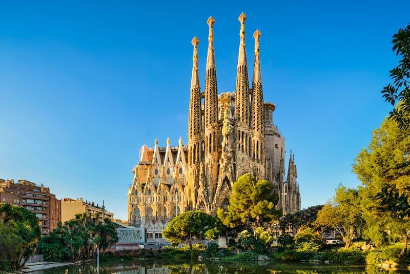 Fotografia esterno Sagrada Familia cielo azzurro ed alberi attorno
