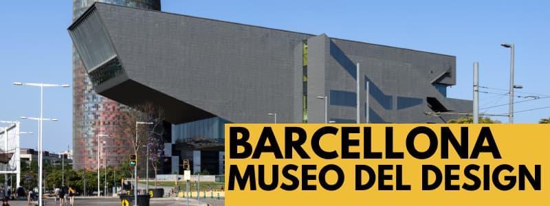 """Fotografia dall'esterno del Museo del Design di Barcellona con struttura a forma di parallelepipedo con una torre accanto con cielo azzurro alle spalle. In basso a destra rettangolo arancione con scritta nera """"Barcellona museo del design"""""""