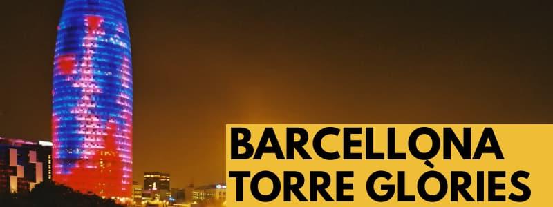 """Fotografia della Torre Glòries di Barcellona di notte, un grattacielo illuminato blu, viola e rosso sulla sinistra con gli altri edifici in basso. In basso a destra rettangolo arancione con scritta nera """"Barcellona Torre Glòries"""""""